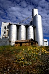 Old abandoned granary or tall grain silos in rural area with blue sky and dramatic white clouds