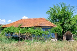 Old abandoned hose with tiled roof in the village . Ancient hovel and cellar