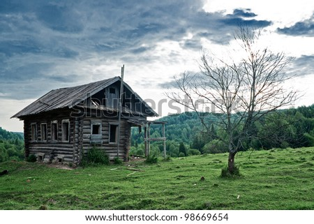 Old abandoned house and dead tree in Russian north