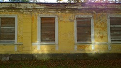 Old abandoned house in disrepair. Windows are filled with wooden planks instead of glass. Poverty, devastation, economic, financial and housing development crisis. Social problems concept. Sunny ray.