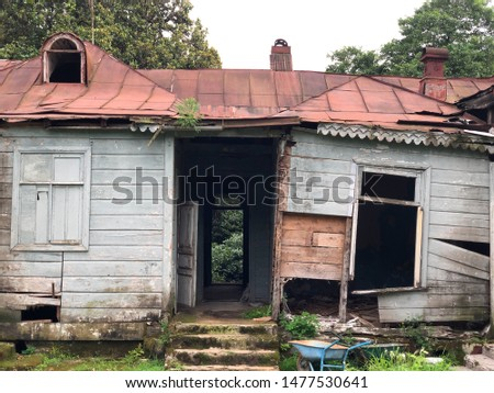 Old abandoned house on green grass surrounded by nature. House without windows and doors in the forest. The mansion in which no one lives. stock photo