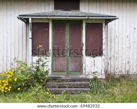 Old abandoned house with flowers in the garden