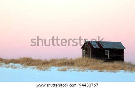 Old, abandoned one room farm house at sunset.  Winter in Wisconsin