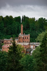 Old abandoned paper mill built with red bricks surrounded by forest