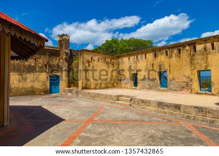 Old abandoned prison on Changuu ( Prison ) Island, Zanzibar, Tanzania. Courtyard with a stone wall on the background of  cloudy sky. Tourism destination, tourist attraction