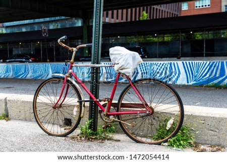 Old abandoned red bicycle next to road bridge next in Manhattan, New York City, USA #1472054414