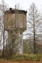 old abandoned ruined water tower in the forest