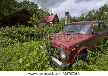 old abandoned russian red car in nettles