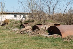 Old abandoned rusty barrels lie half buried in the ground.