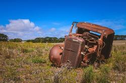 Old abandoned rusty car wreck in rural Australian farm field