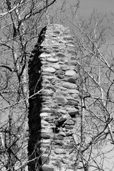 Old abandoned stone chimney remaining from homestead overgrown and fallen into disrepair black and white portrait
