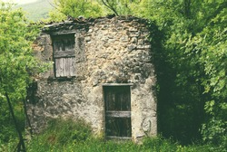 Old abandoned stone house, in the woods in spring
