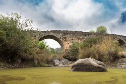 old abandoned stone roman bridge with dry riverbed