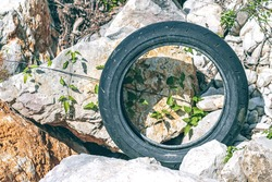old abandoned tire amid rocks on the riverbank,pollution concept