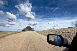 Old abandoned traditional brick house (shed), close-up view from a car. A dirt road in Kurzeme, Latvia. Idyllic rural scene. Clear sky with cirrus and cumulus clouds. Architecture, travel destinations