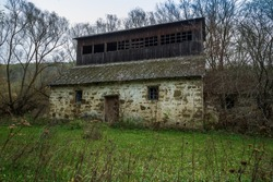 Old abandoned water mill in the forest. Abandoned building.