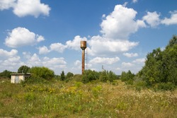 Old abandoned watertower in a countryside.