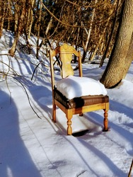 old abandoned wooden chair in snowy woods