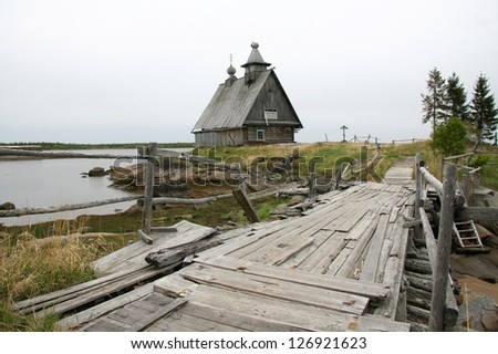 Old abandoned wooden church on the island on a cloudy day and the old wooden bridge. Karelia, Kem