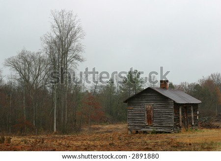 Old abandoned wooden house in a clearing by the woods