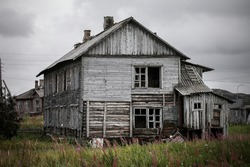 Old abandoned wooden house over the cloudy sky