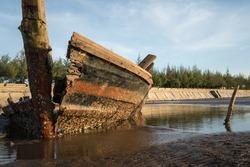 Old abandoned wreck ship unused small boat at sea coast