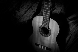 Old acoustic guitar, classical musical instrument, in black and white style. Suitable for art backgrounds or illustrations.