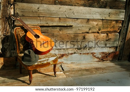 old acoustic guitar on an old armchair horizontal