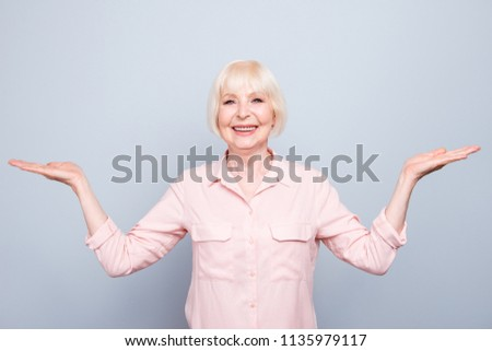 Old adult blonde glad cheerful lady smiling, showing gesture with hands, palms two sides, over grey background, looking straight, isolated