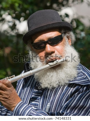 Old African American musician playing flute outdoors