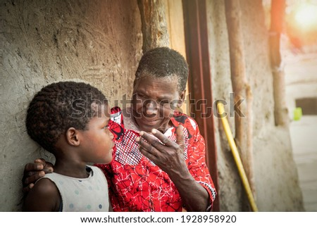 old African woman telling a story to her granddaughter sitting in her yard in a village in Botswana Foto stock ©