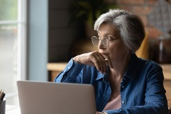 Old age and tech. Thoughtful aged latin female sit at desk work online by laptop from home office. Pensive lady retiree learn to use internet study computer ponder on next step distracted from screen