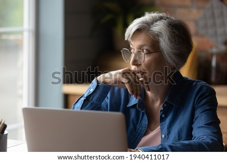 Old age and tech. Thoughtful aged latin female sit at desk work online by laptop from home office. Pensive lady retiree learn to use internet study computer ponder on next step distracted from screen Foto stock ©