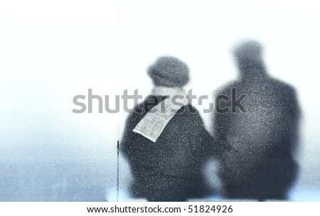 old age - old couple sitting in a bus stop