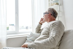 old age, problem and people concept - senior man in glasses thinking and looking through window at home