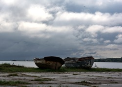 Old age. Two old boats on the bay.