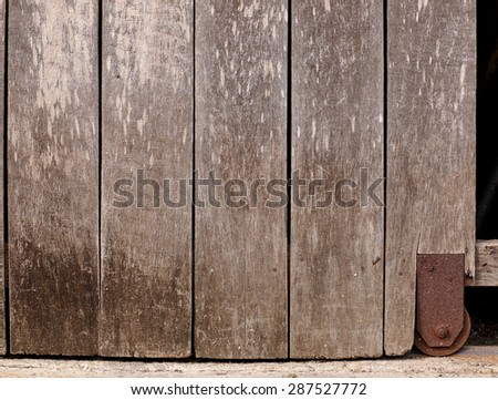 old aged abandoned weathered wood surface of a gray color old country house door with rusty metal door fittings installed