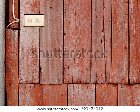 old aged abandoned weathered wood surface of a red brown color old country house external wall with white plastic electric switches installed