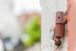 Old aged metal rusty metal door hinge closeup / old rusty hinge / Close up of a rusted hinge with weathered metal door