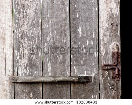 old aged weathered wood surface of an old country house door with wooden grip and rusty bolt.