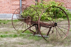 Old agricultural machinery with large wheels in a rural yard. Old and rusty plow abandoned