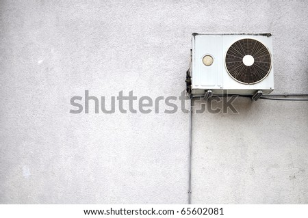 Old air conditioner mounted outside on a grey wall