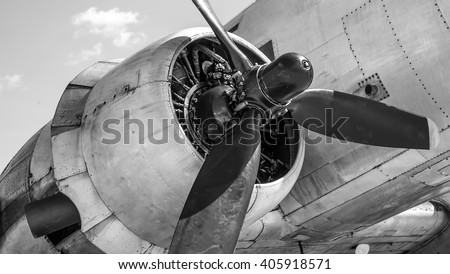 old airplane engine with a propeller and the nacelle on the background of the fuselage