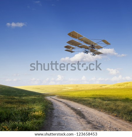 Old airplane flying above the beautiful green field