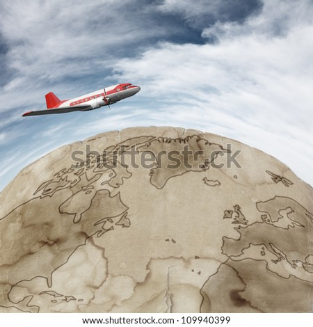 Old airplane flying against blue sky over rusted earth map