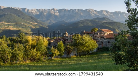 Old alpine village called Travesseres with an imposing mountain chain in the background at golden hour. Beautiful panorama in Serra del Cadi, Pyrenees, in Catalonia (Catalunya), Spain.  Zdjęcia stock ©