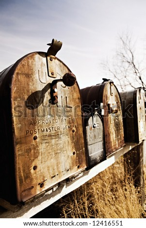Old American mailboxes in late sun, rusting away in rural Midwest.