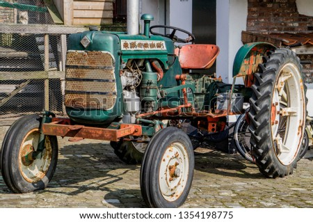 Old American tractor in good condition at farm yard restored looking vintage slightly rusty