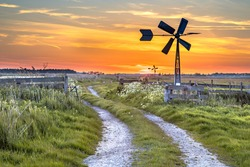 Old american windmill at sunset in dutch rural landscape near Jisp, Noord Holland, Netherlands