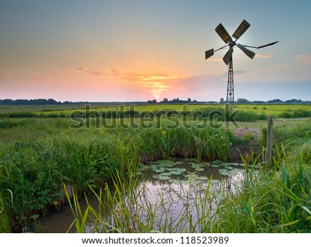 Old american windmill during sunset in dutch rural setting